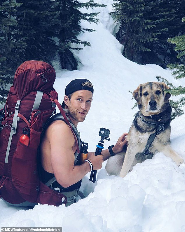 Intrepid: Armed with a camera, Michael and BearBear pose for a photo in the deep snow. Michael moved into an RV to pursue his adventuring after the end of a relationship last year
